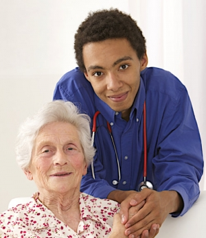 young caregiver smiling and holding his patient's hands