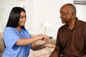 caregiver helping an elderly patient take his pills